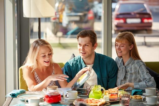 Gelukkig kaukasische vrienden rusten in café met maaltijd en plezier