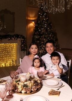 Gelukkig kerstdiner, aziatische familie met kinderen lachend bij de open haard en de kerstboom