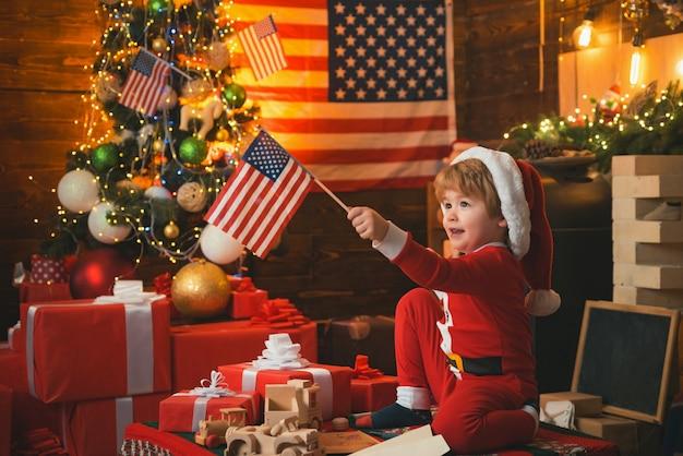 Gelukkig kerstfeest jongen met vlaggen van de vs.