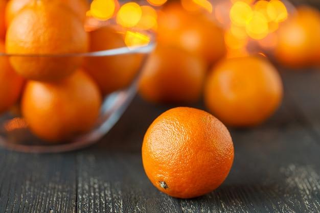 Gelukkig kerstfeest of nieuwjaarskaart. nieuwjaar of kerstversiering met mandarijnen en kerstverlichting