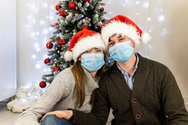 Gelukkig kerstpaar samen: man en vrouw omhelzen elkaar en glimlachen.