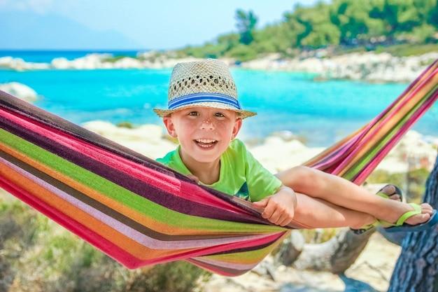 Gelukkig kind aan zee op hangmat op de achtergrond van griekenland