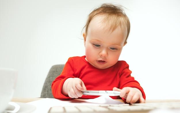 Gelukkig kind babymeisje peuterzitting met toetsenbord van computer geïsoleerd op een witte achtergrond