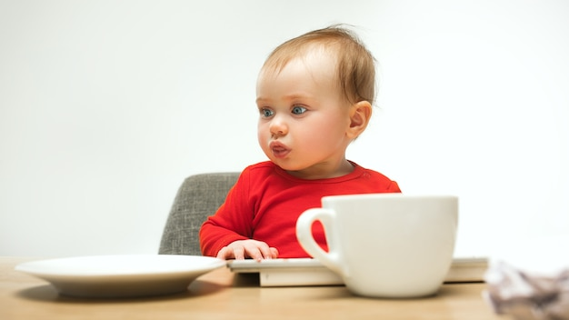 Gelukkig kind babymeisje zit met toetsenbord van moderne computer of laptop in wit
