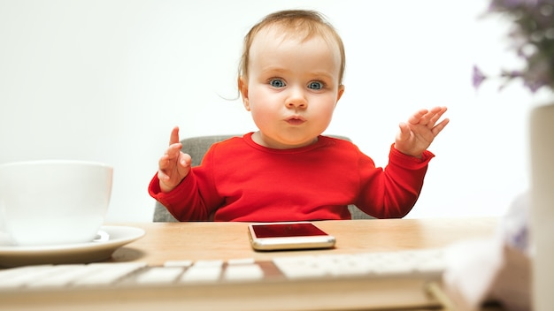 Gelukkig kind babymeisje zit met toetsenbord van moderne computer of laptop in witte studio