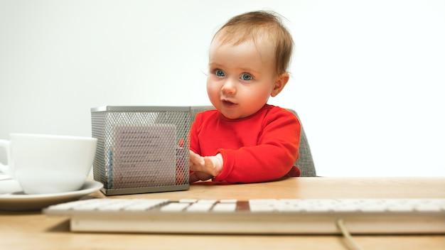 Gelukkig kind babymeisje zit met toetsenbord van moderne computer of laptop in witte studio.