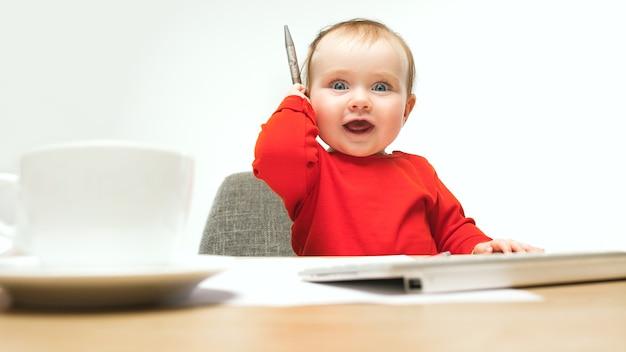 Gelukkig kind babymeisje zitten met pen en toetsenbord van moderne computer of laptop geïsoleerd op een witte studio.