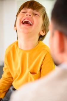 Gelukkig kind dat een geel overhemd draagt