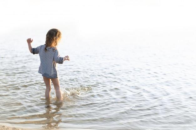 Gelukkig kind dat en in de golven tijdens de zomervakantie loopt springt. vakantie aan zee of oceaan kust voor gezin met jonge kinderen. kinderen spelen aan zee. meisje doet splases met benen.