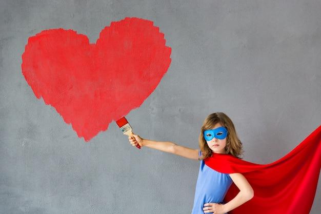 Gelukkig kind dat groot rood hart op de muur schildert. grappig superheldenmeisje dat thuis speelt. valentijnsdag kaart. renovatie en ontwerpconcept