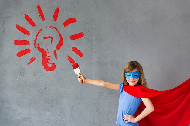 Gelukkig kind dat grote rode gloeilamp op de muur schildert, huisrenovatie en idee-ontwerpconcept