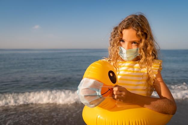 Gelukkig kind dat medisch masker draagt openlucht tegen blauwe hemelmuur.