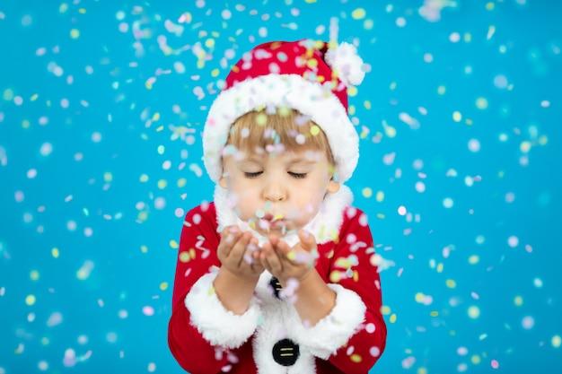 Gelukkig kind dat santa claus-kostuum draagt. kid waait confetti tegen blauwe muur. kerst vakantie concept