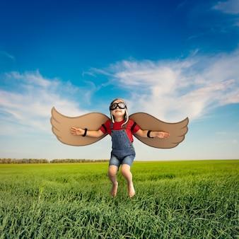 Gelukkig kind dat tegen blauwe hemel springt