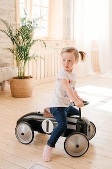 Gelukkig kind dat thuis speelt. een meisje met paardenstaarten speelt in de kamer en rijdt in een retro speelgoedauto.