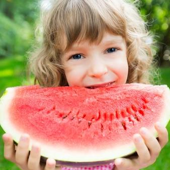 Gelukkig kind dat watermeloen buiten eet in het zomerpark
