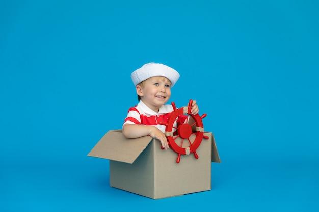 Gelukkig kind droomt ervan kapitein te worden tegen een blauwe muur.