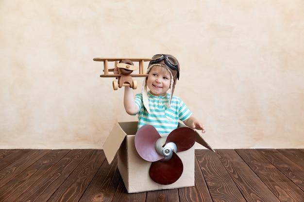 Gelukkig kind droomt ervan piloot te worden in een kartonnen doos.