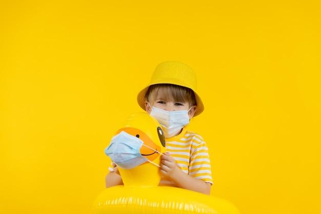 Gelukkig kind droomt van vakantie. portret van jong geitje dat beschermend masker binnen draagt.