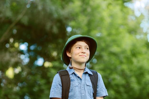 Gelukkig kind gaat wandelen met rugzak in de zomer natuur