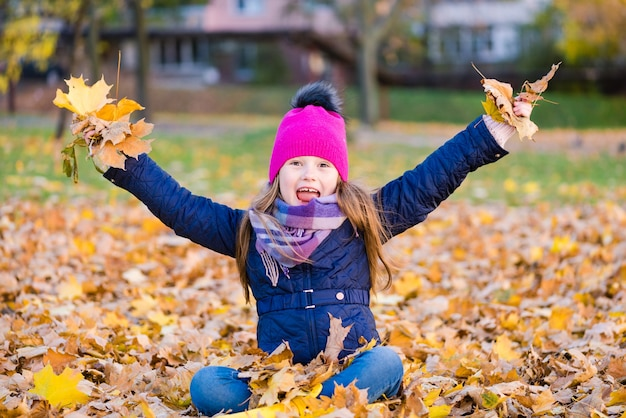 Gelukkig kind gooien herfstbladeren en glimlachen buitenshuis.