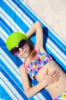 Gelukkig kind in glazen die op de kustachtergrond zonnebaden