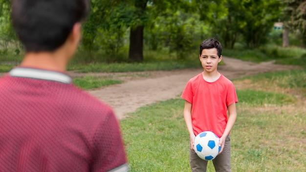 Gelukkig kind in het rood shirt spelen met de bal