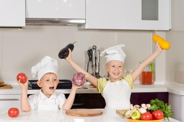 Gelukkig kind in kokskleding met verse groenten in de keuken