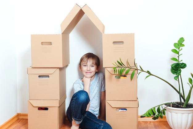 Gelukkig kind in nieuw huis. huisvesting van een jong gezin met een kind. familie verhuist naar een nieuw appartement. jongen speelt in hun nieuwe appartement. schattige jongen helpt dozen uitpakken.
