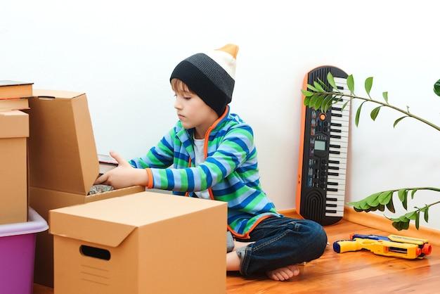 Gelukkig kind in nieuw huis. huisvesting van een jong gezin met een kind. familie verhuist naar een nieuw appartement.