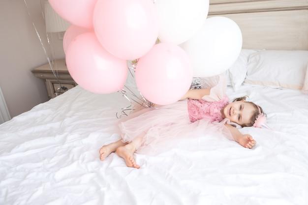Gelukkig kind in roze feestelijke jurk verjaardagspet ligt op een gezellig wit bed met banch-verjaardagsballonnen