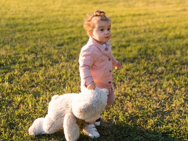 Gelukkig kind in roze kleding en zijn vriendelijke speelgoed