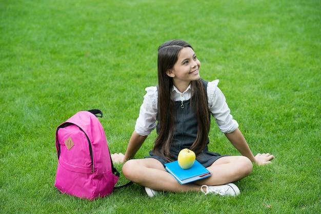 Gelukkig kind in schooluniform ontspannen met boek en appel gezonde voeding op groen gras, dieet.