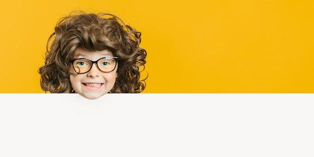 Gelukkig kind jongen bedrijf kijkt door een stuk papier voor tekst