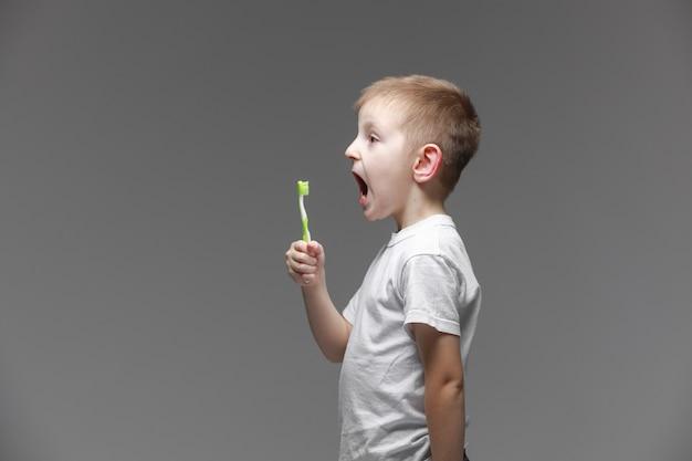 Gelukkig kind jongen jongen met elektrische tandenborstel op grijze achtergrond. gezondheidszorg, mondhygiëne. mockup, kopieer ruimte.