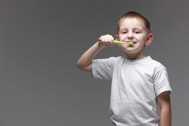 Gelukkig kind jongen jongen tanden poetsen met tandenborstel op grijze achtergrond. gezondheidszorg, mondhygiëne. mockup, kopieer ruimte. Premium Foto