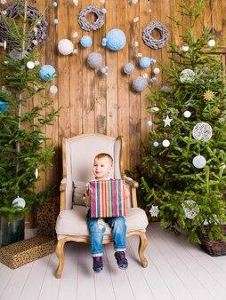 Gelukkig kind jongen met geschenkdoos in de buurt van de kerstboom.