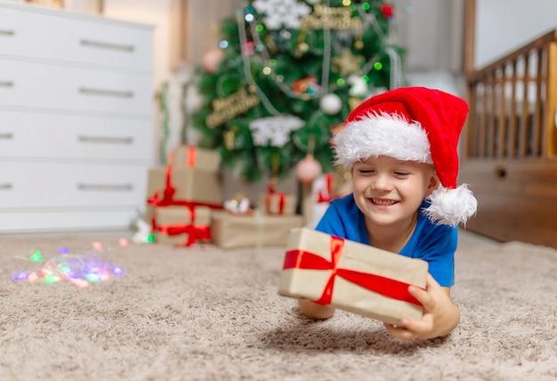 Gelukkig kind jongen op kerstmis op gezellig tapijt in zijn kamer in pyjama en rode kerstmuts open geschenken