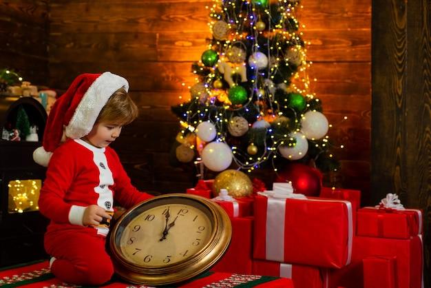 Gelukkig kind kijkt naar de grote klok in kerstmuts. kid wacht op het nieuwe jaar. kerst concept. vakantie. kerstkind dromen.