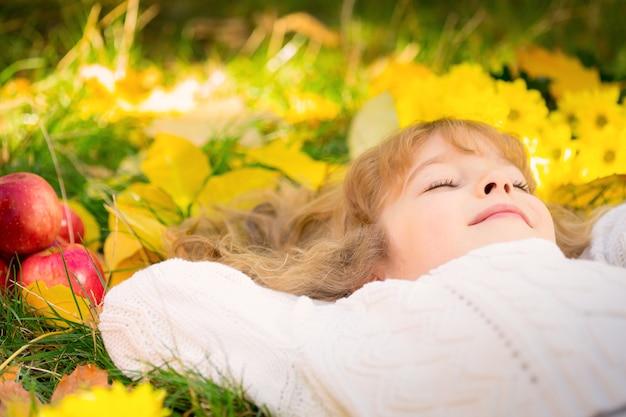 Gelukkig kind liggend op herfstbladeren. grappig kind buiten in het herfstpark
