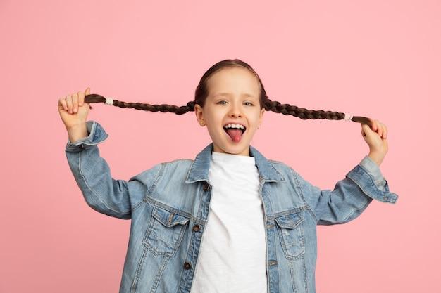 Gelukkig kind, meisje geïsoleerd op de muur. ziet er vrolijk, vrolijk uit. copyspace jeugd, onderwijs, emoties, zaken, gezichtsuitdrukking concept. hoog springen, rennen vieren