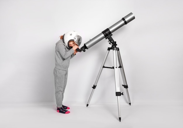 Gelukkig kind meisje gekleed in een astronautenkostuum kijkt door een grote telescoop.