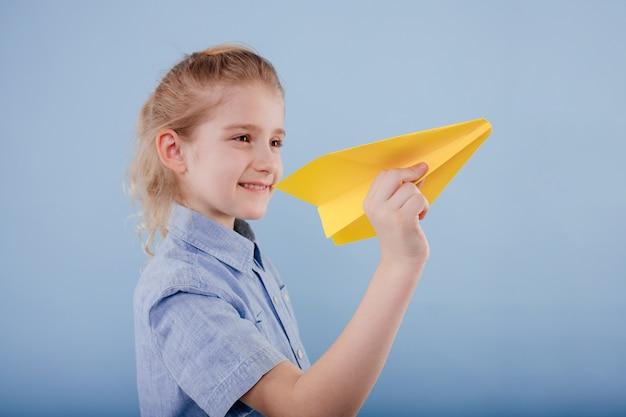Gelukkig kind meisje houdt geel papieren vliegtuigje in zijn hand, geïsoleerd op blauwe achtergrond, kopieer ruimte