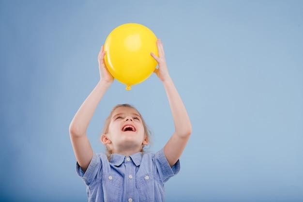 Gelukkig kind meisje houdt gele ballon geïsoleerd op blauwe achtergrond kopie ruimte