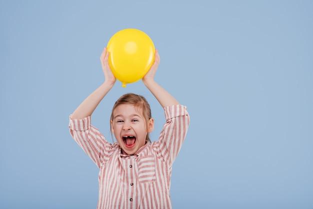 Gelukkig kind meisje houdt gele ballon gekleed in gestreept shirt geïsoleerd op blauwe achtergrond kopie s...