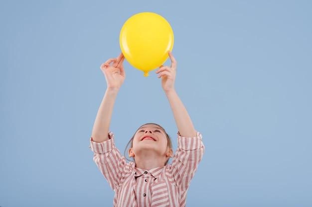Gelukkig kind meisje houdt gele ballon omhoog gekleed in gestreept shirt geïsoleerd op blauwe achtergrond kopie ruimte