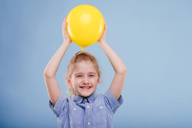 Gelukkig kind meisje houdt gele ballon omhoog met een glimlach geïsoleerd op blauwe achtergrond kopie ruimte
