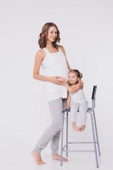 Gelukkig kind meisje knuffelen zwangere moeders buik, zwangerschap en nieuw leven.