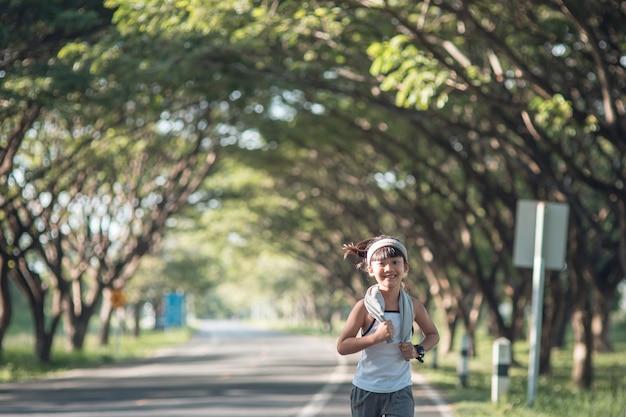 Gelukkig kind meisje loopt in het park in de zomer in de natuur. warme zonnevlam.
