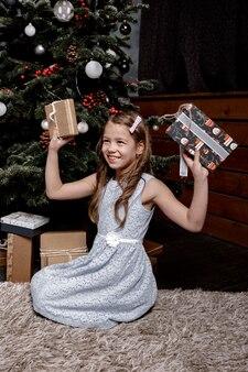 Gelukkig kind meisje met geschenken op de vloer in de woonkamer bij de kerstboom.